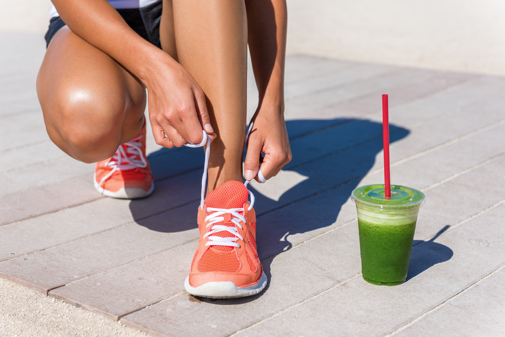 Running woman athlete runner getting ready for beach morning run by tying shoe laces of running shoes with green vegetable smoothie breakfast.