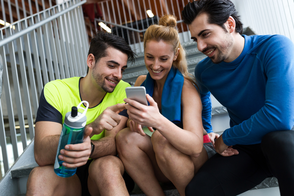 Portrait of group of sporty people using mobile phone in gym.