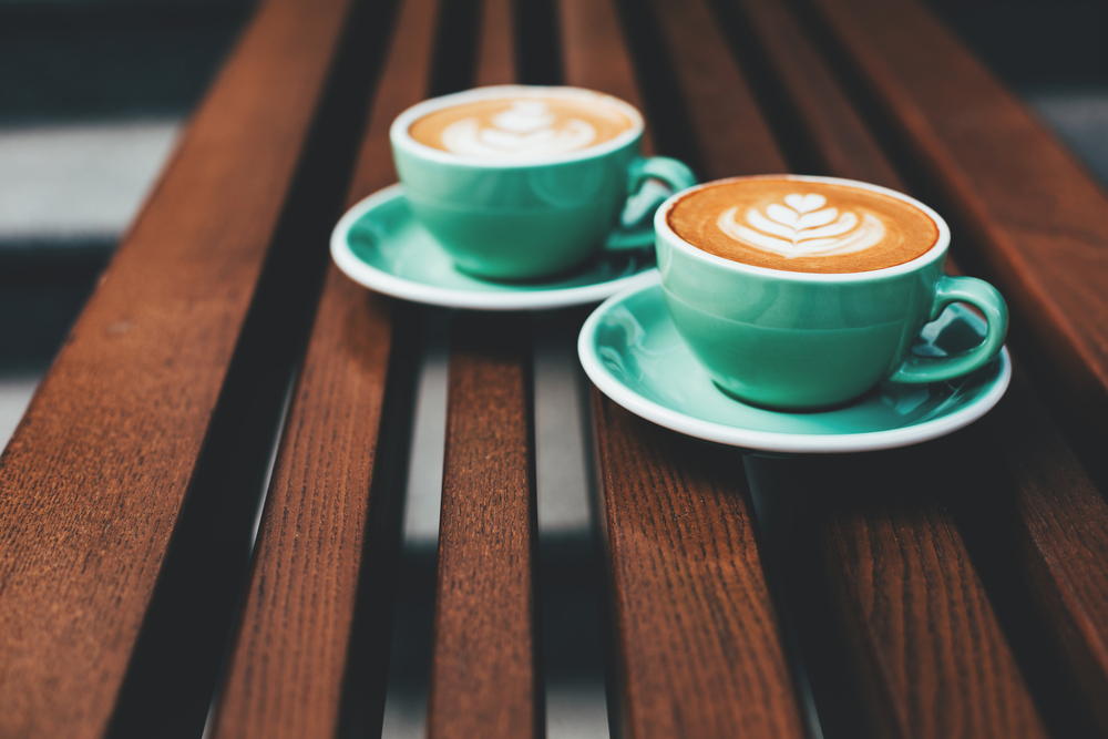 Two cups of cappuccino with latte art on wooden background