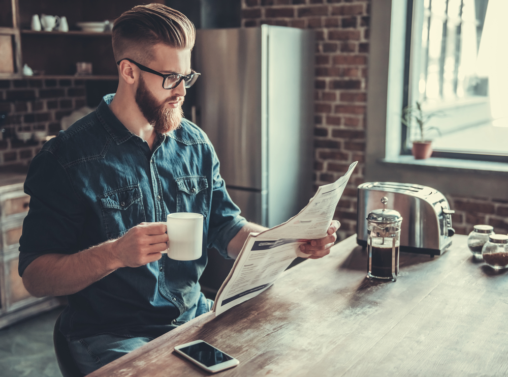 Young man is drinking coffee and reading a newspaper while resting in kitchen