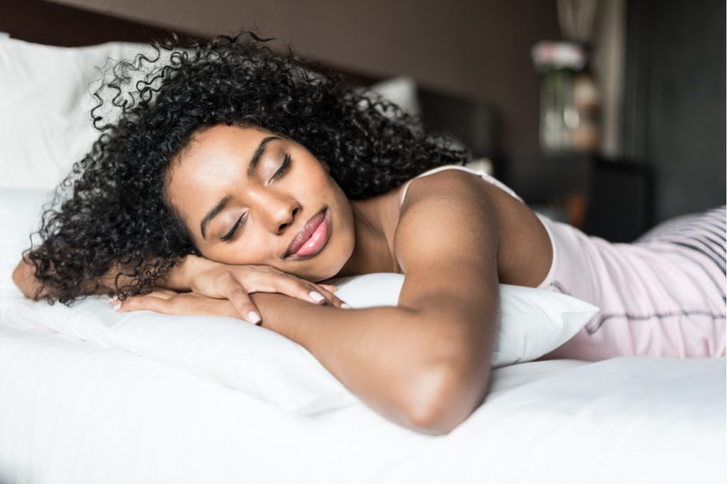 Woman happy sleeping in white cover bed.