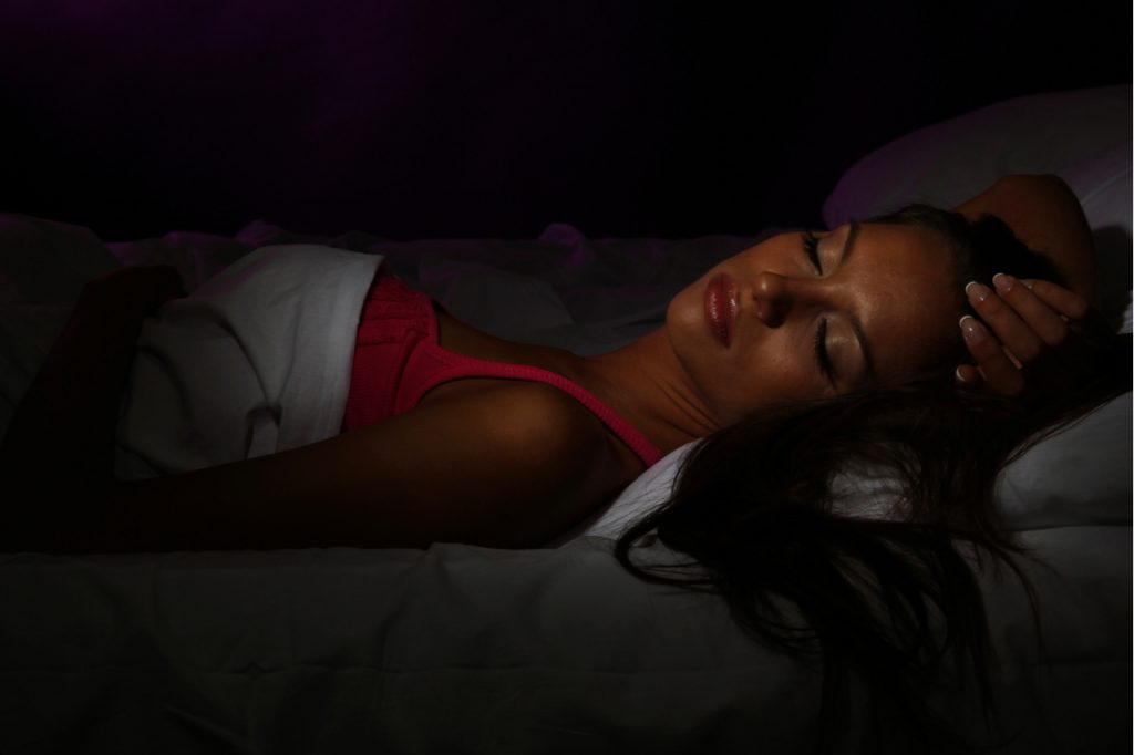 A woman sleeping in a very dark room.