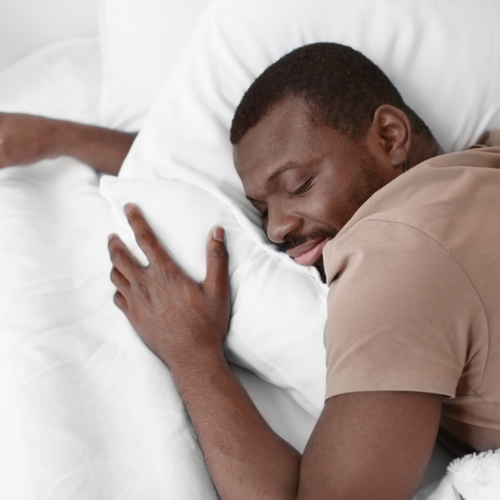 A man sleeping comfortably in his bed.