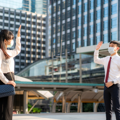 Business man and woman greet and say hello with business colleague and wearing mask standing distance of 1 meter distance protect from COVID-19