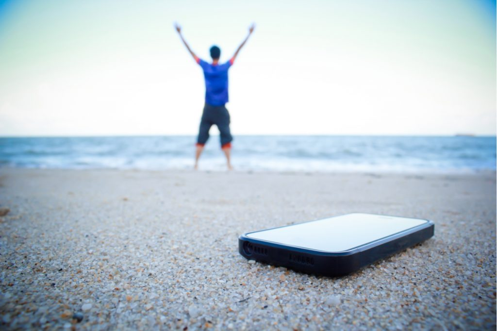 A man put smart phone on the beach sand and turned it off.