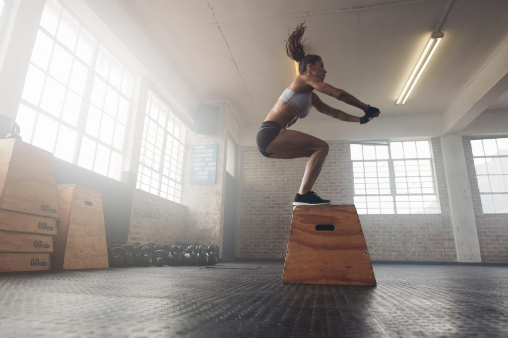 Side view image of fit young woman doing a box jump exercise