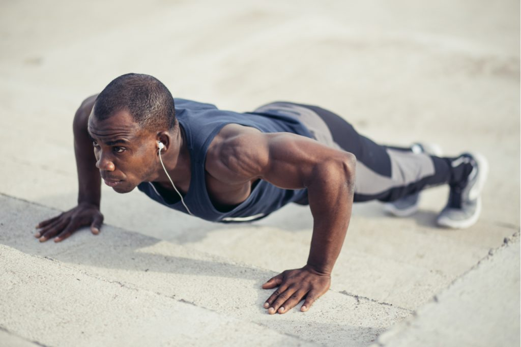 Portrait of a man doing push ups at the beach.