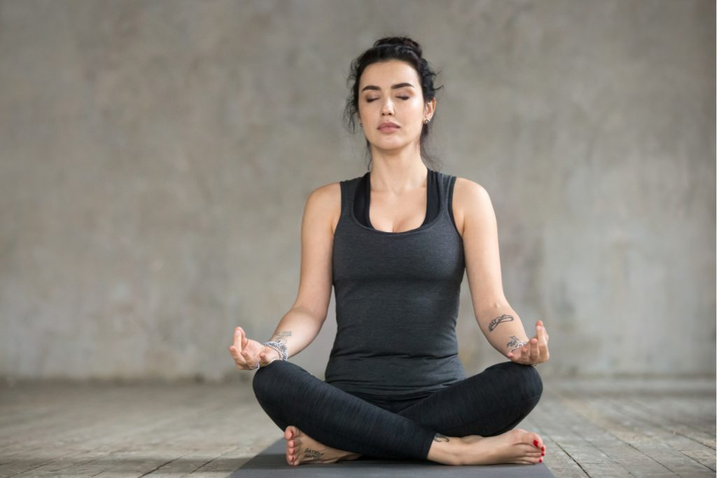 A woman wearing dark gray clothing doing the sukhasana yoga pose.