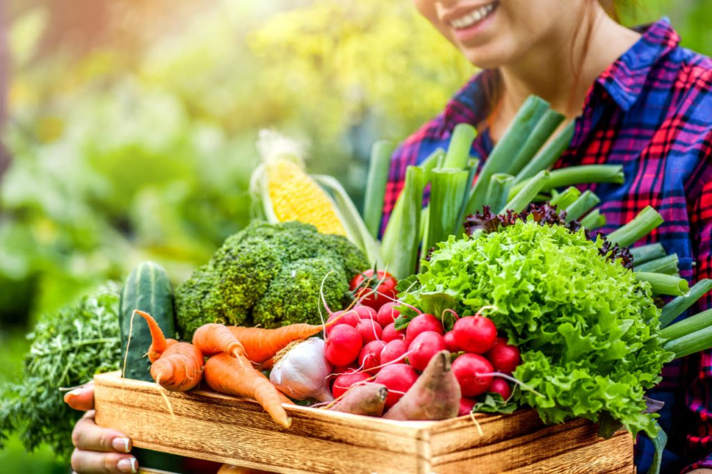 A woman holding a crate of fresh vegetables.