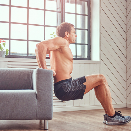 Muscular male does exercise leaning on a sofa at home.