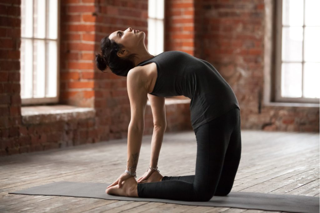 A woman doing the ustrasana yoga pose or camel pose.
