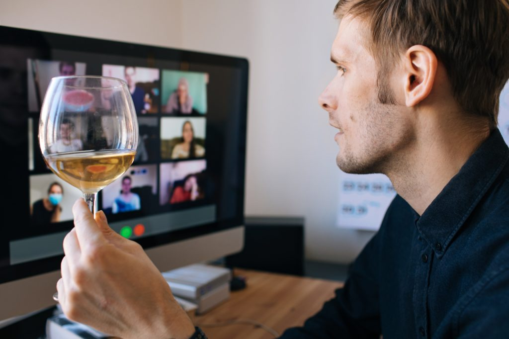 A man holding a wine glass while on a video conference call with his friends.
