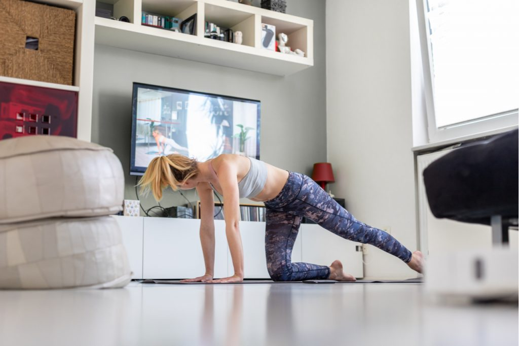 Attractive sporty woman exercising in front of television in her living room.