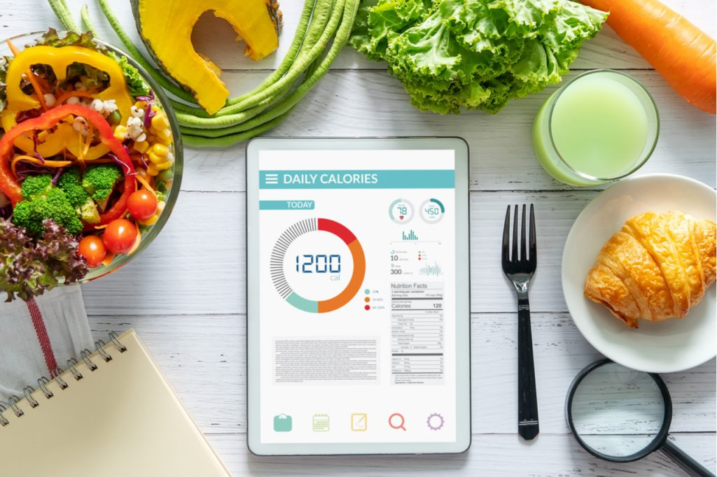 App on a tablet showing daily calories, next to some vegetables and a croissant on a white table.