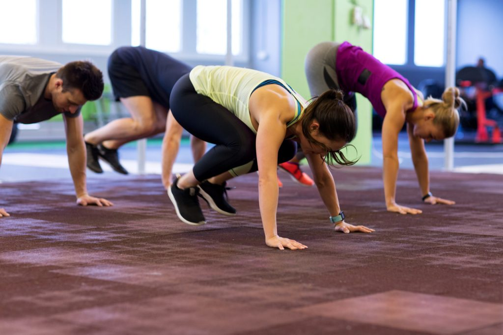 Group of people exercising doing burpees workout.