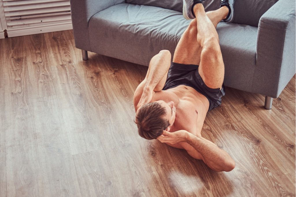 Muscular male doing abdominal exercises on floor at home for muscle contraction.