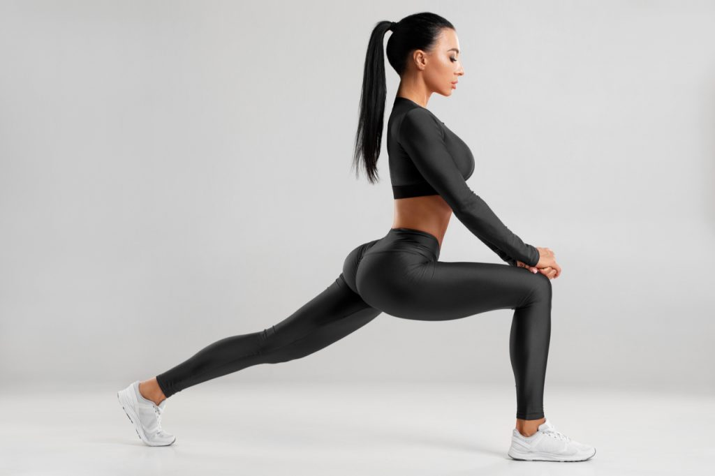 A fit woman doing front forward one leg step lunge exercise for butt.