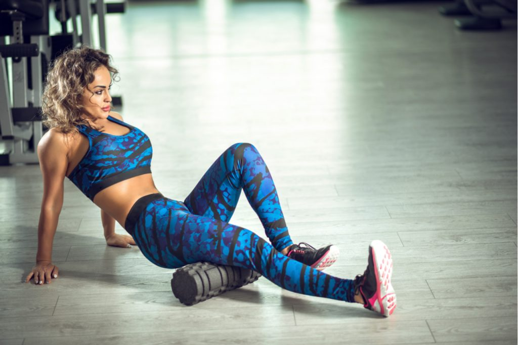 Woman doing foam roller exercise and posing in modern bright fitness center.