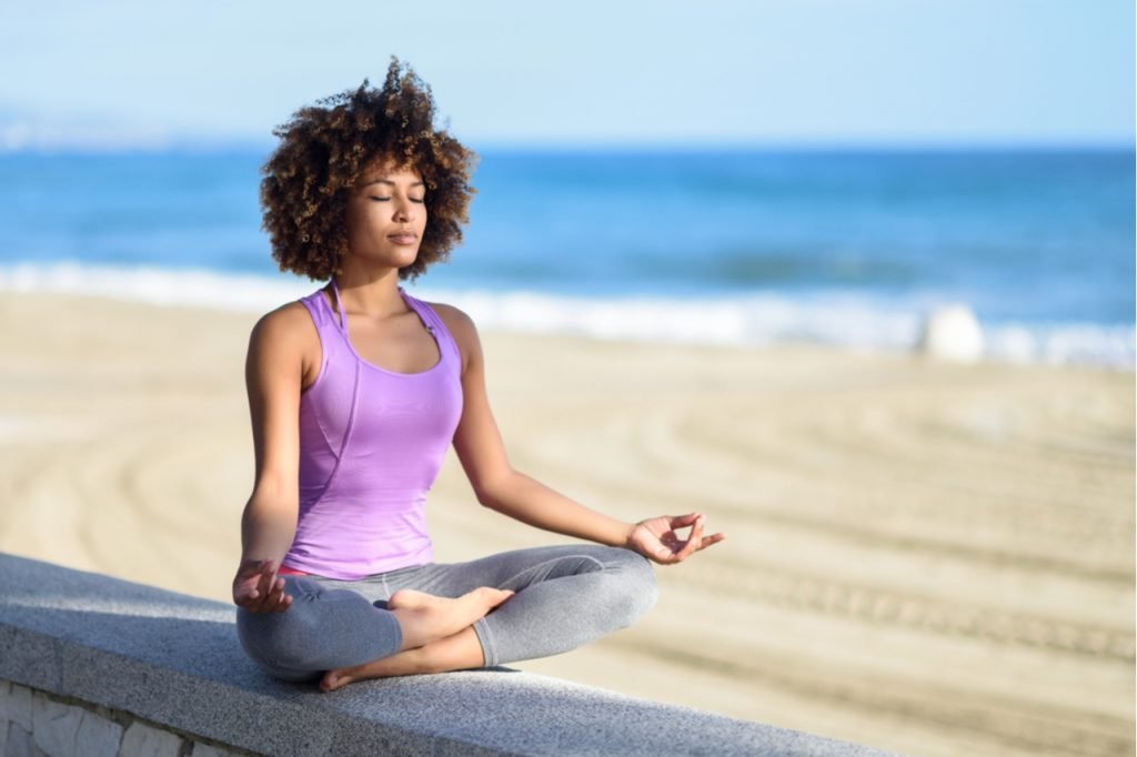 Woman doing yoga asana in the beach with eyes closed