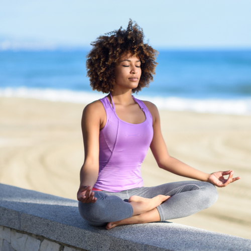 A woman meditating as part of yoga by the beach.