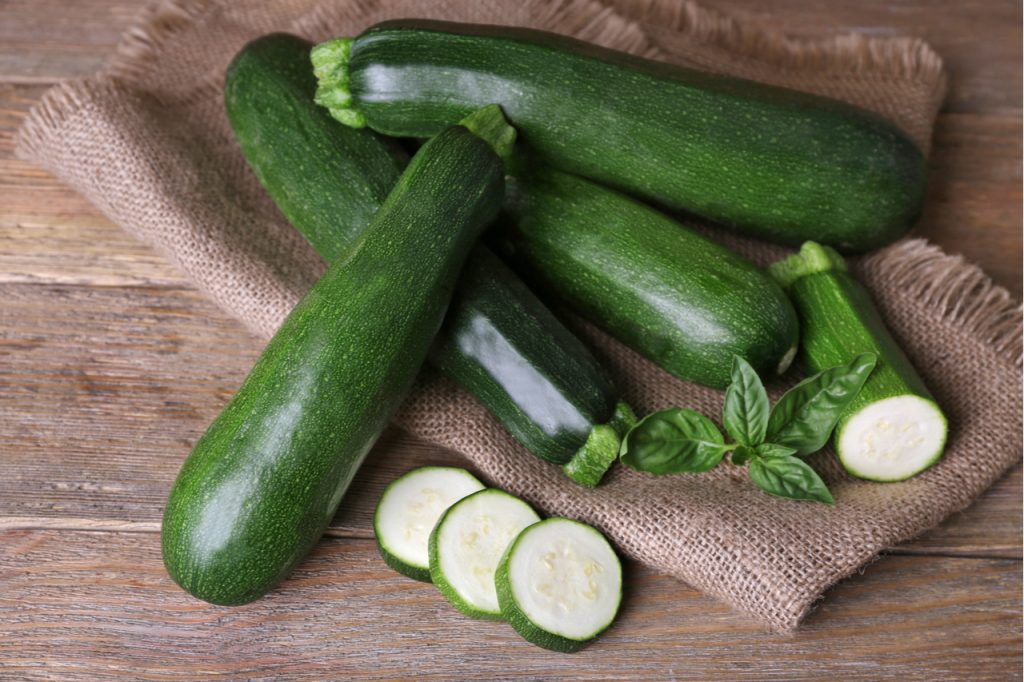 A close up image of 5 zucchinis on a wooden table.