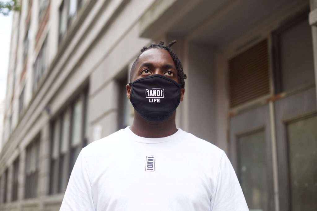 model wearing a reusable face mask with 1AND1 Life logo