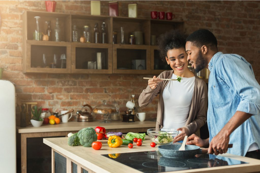 A young African American couple preparing salad together.
