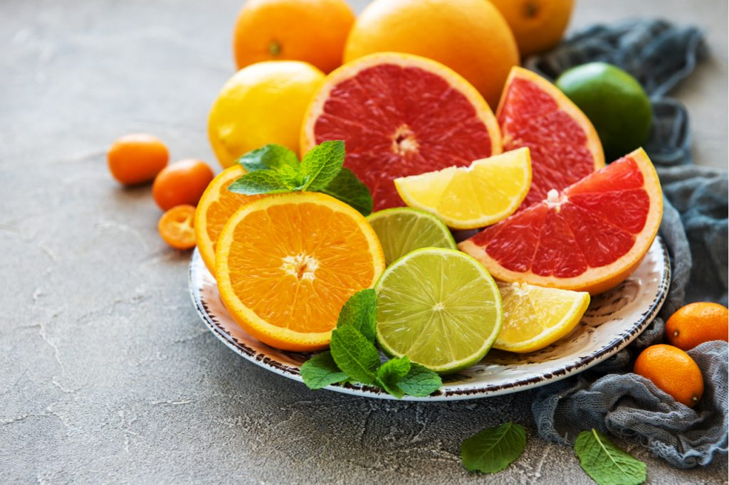 Sliced orange, lime, and lemon on a platter. Eat fruits rich in vitamin C that is how to boost the immune system.