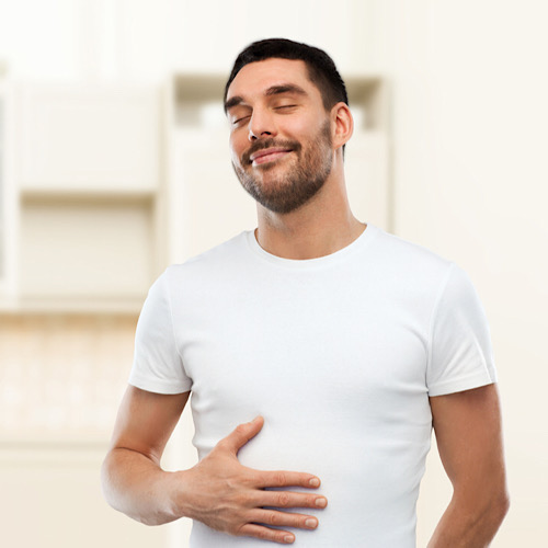 happy full man touching his tummy over kitchen background