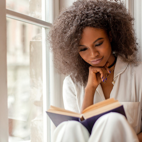 afro-american girl with reading a book sitting on the windowsill.