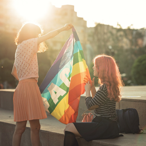 two women holding lgbt flags