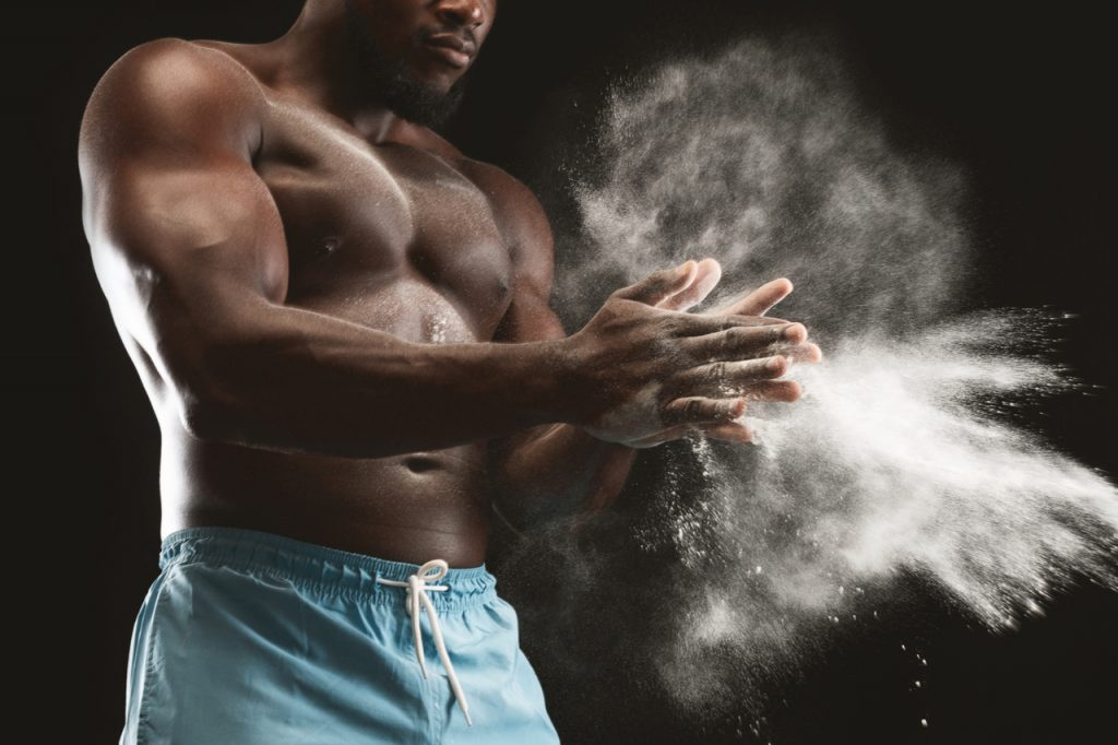 Muscular man clapping hands with magnesium powder and preparing for workout at gym.