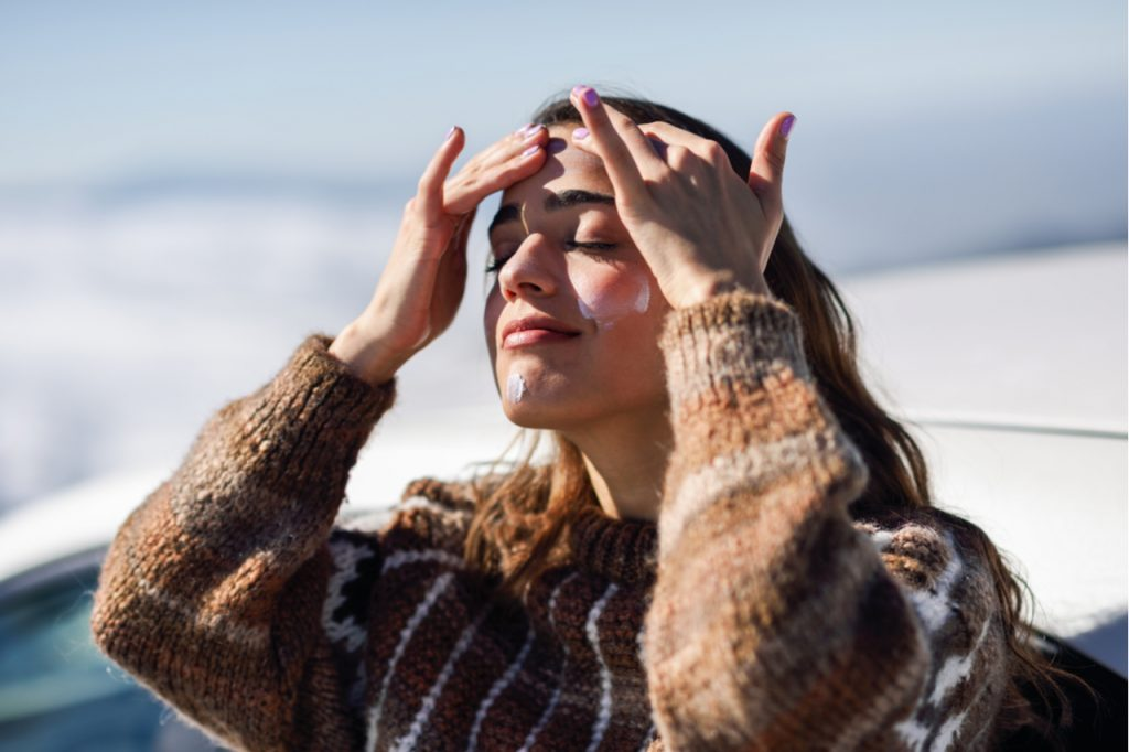 A woman on a sweater applying sun screen on her face for sun protection during winter months.