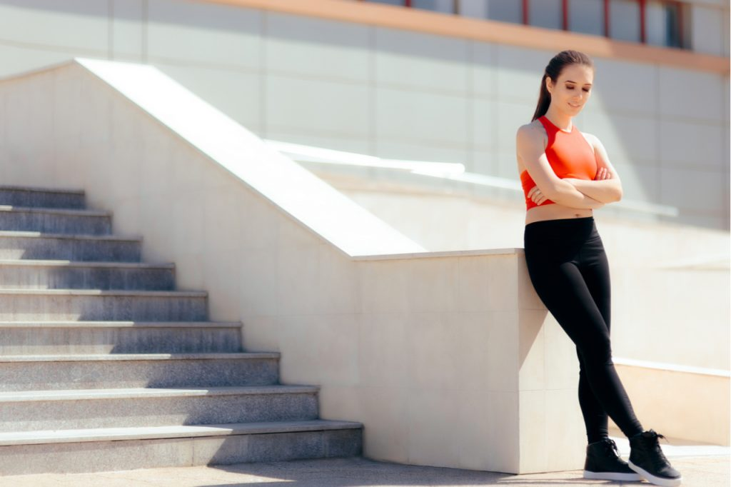 A fit woman wearing fitness clothes while resting near the stairs.