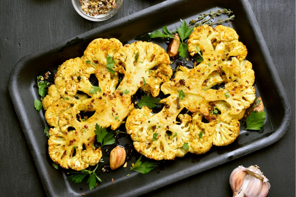 Baked cauliflower with some herbs on baking pan. Getting nutrients from vegetables means knowing which vegetables retains their nutritional content with heat.