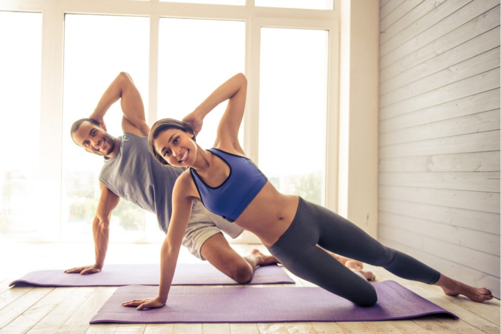 Couple in sports clothes is looking at camera and smiling while working out on yoga mat at home.
