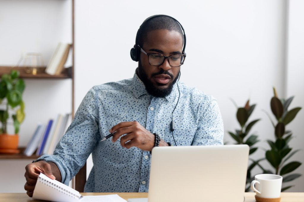 Man sitting at table wearing headphones listening to an audio file.