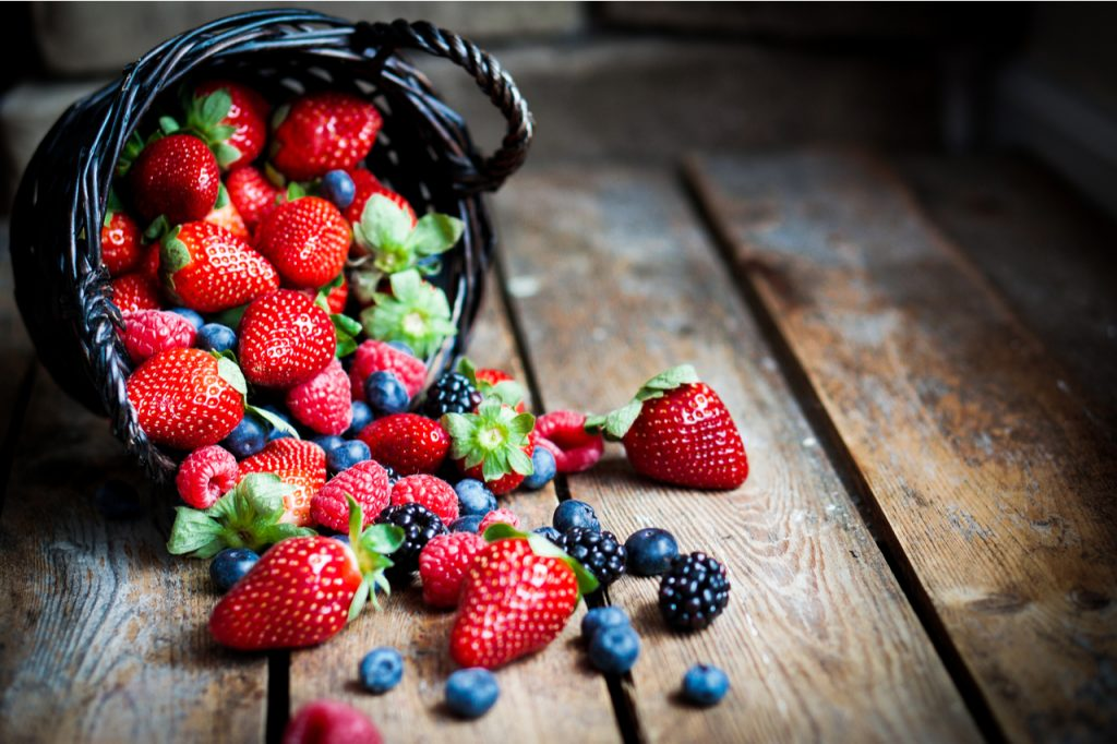 Mix of fresh berries in a basket on rustic wooden background.
