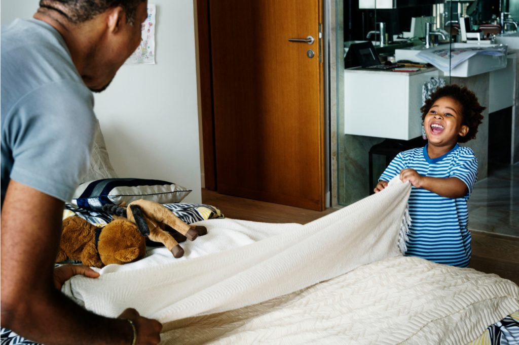 Father and son changing bedding or sheets on a bed.