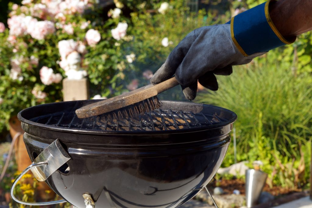 Male hand with gloves cleans round grill with stiff brush.