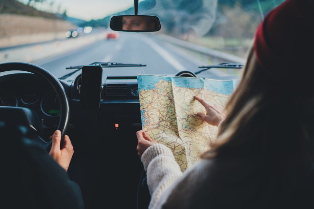 Couple in a car on a road trip, woman checking a map guiding her husband while he drives.