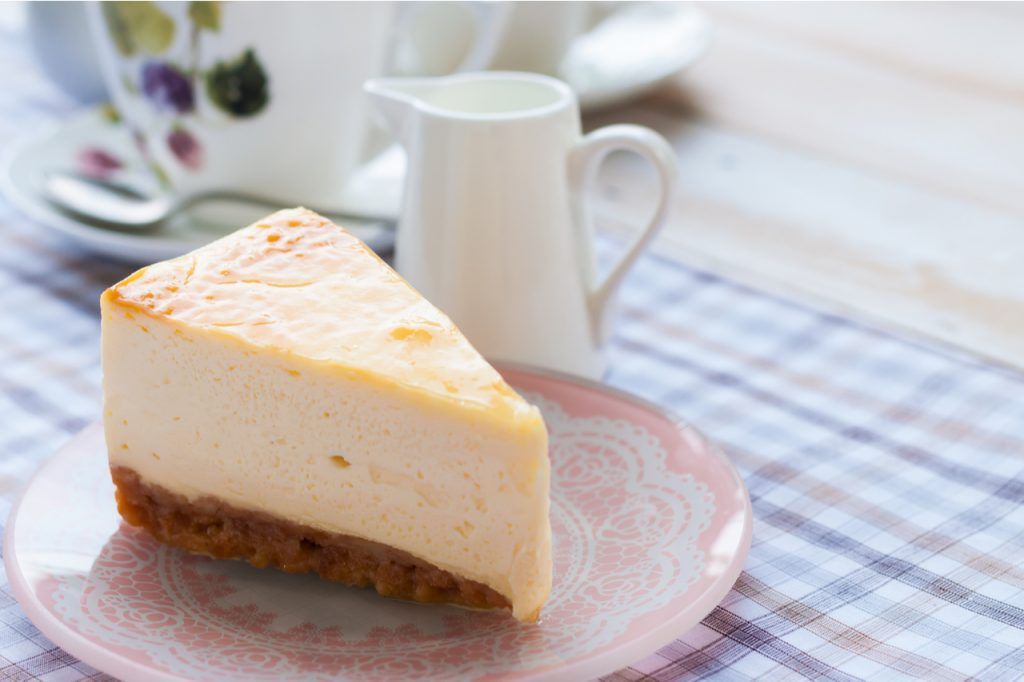 Slice of new york style cheesecake with a cup of tea.