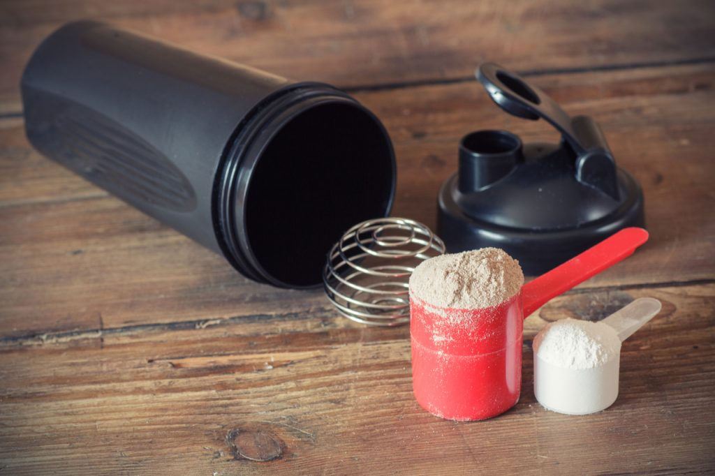 Creatine powder in scoop and plastic shaker on wooden background.