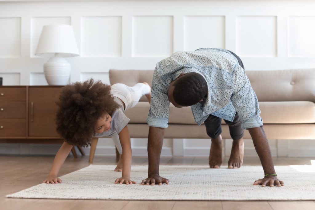 Father and daughter in casual clothes do pushup pressup exercise on carpet on warm floor in living room.