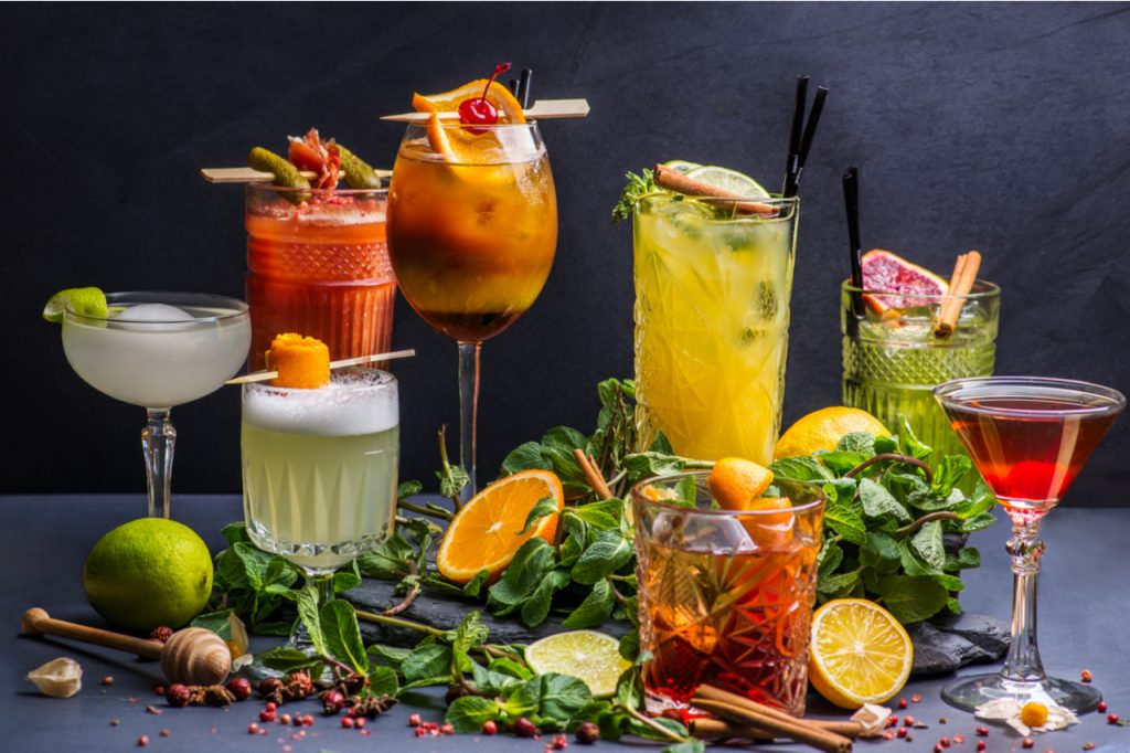 A variety of healthy cocktails surrounded by slices of lemon, oranges and mint leaves.