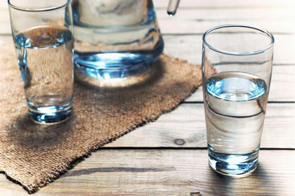 Glasses of water on a wooden table. Selective focus.