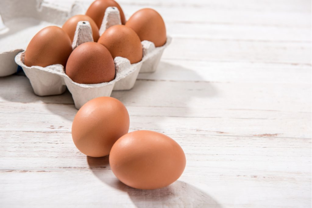Close-up view of raw chicken eggs in egg box on white wooden background.