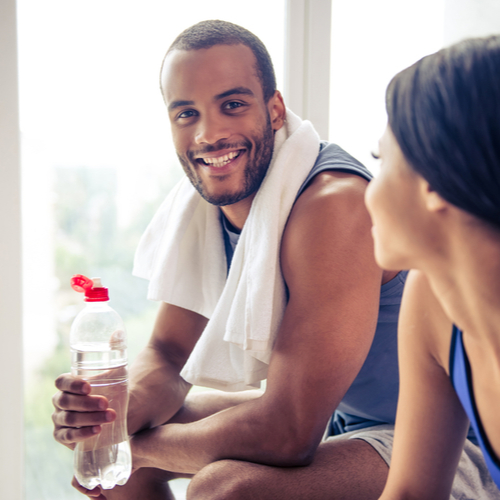 Couple in sports clothes resting after workout.