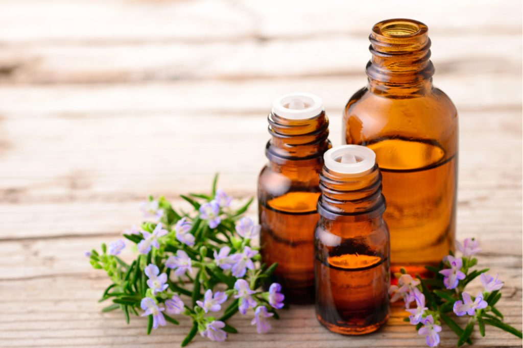 3 bottles of essential oils with small flowers on the side on a wooden surface.