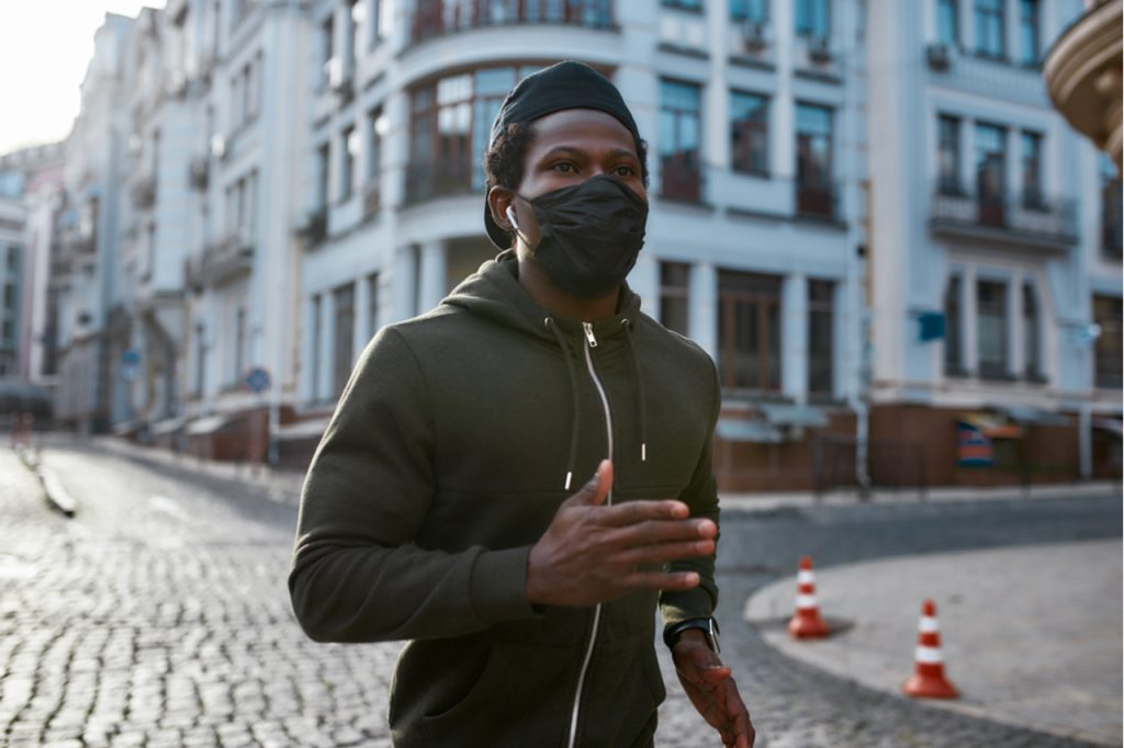 Man in black sportswear and medical protective mask running through the city street in the morning.